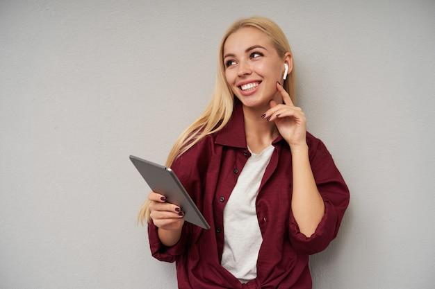 Foto interna de uma jovem atraente com longos cabelos loiros tocando suavemente seu pescoço enquanto olha para o lado com um sorriso encantador, vestindo uma camisa bordô e uma camiseta branca sobre fundo cinza claro