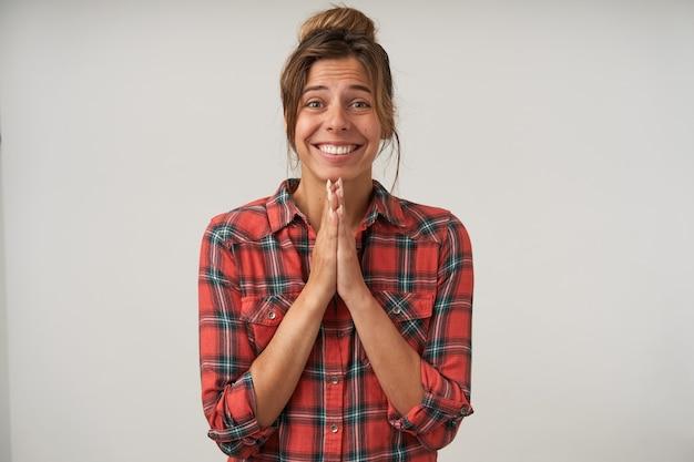 Foto interna de uma jovem atraente de cabelos castanhos com maquiagem natural, mantendo as palmas das mãos levantadas juntas, enquanto olha esperançosamente para a câmera, posando sobre fundo branco