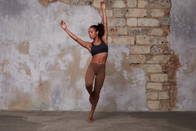 Foto interna de uma jovem atraente de pele escura com cabelo castanho cacheado ensaiando dança contemporânea, concentrada enquanto mantém as mãos sob a cabeça