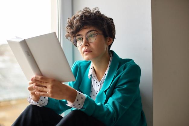Foto interna de uma jovem atraente morena encaracolada de óculos, sentada no parapeito da janela, lendo um livro atentamente interessante e arredondando surpreendentemente seus olhos castanhos enquanto olha para dentro