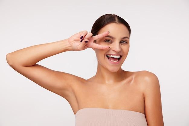 Foto interna de uma jovem atraente morena feliz com maquiagem natural, levantando a mão com o símbolo da paz e sorrindo alegremente em pé
