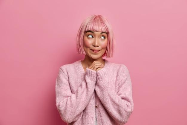 Foto interna de uma jovem bonita e sonhadora com cabelo curto rosa, parece com uma expressão de satisfação feliz à parte, mantém as mãos juntas, usa suéter