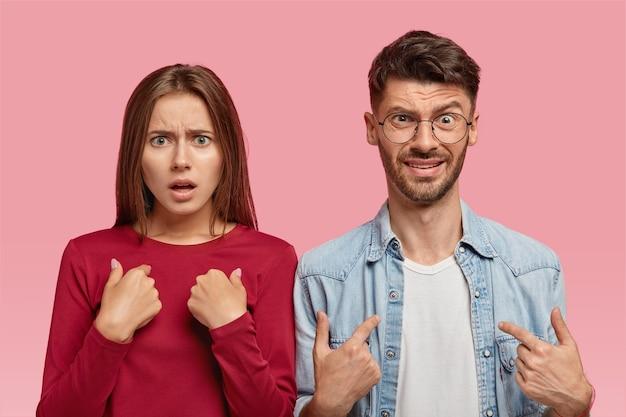 Foto interna de uma jovem caucasiana indignada e um homem apontando para si mesmos