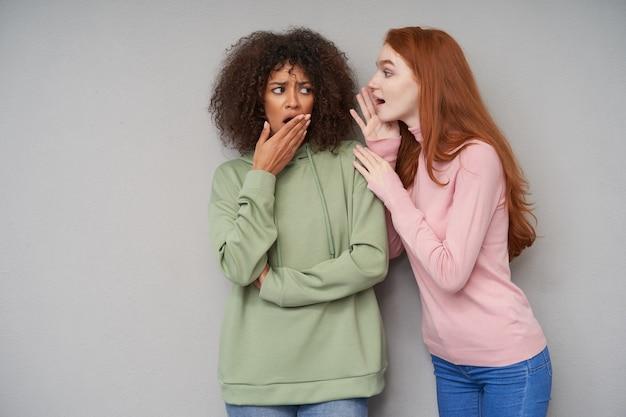 Foto interna de uma jovem confusa mulher encaracolada de cabelos escuros com pele escura, levando a palma da mão à boca enquanto ouve notícias chocantes de sua adorável namorada ruiva de cabelos compridos