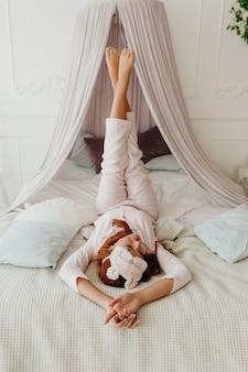 Foto interna de uma jovem de pijama e máscara de dormir deitada na cama com as pernas levantadas