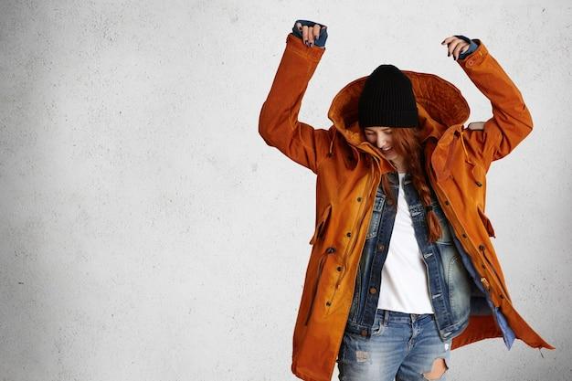 Foto interna de uma jovem e elegante modelo vestindo um casaco de inverno vermelho da moda