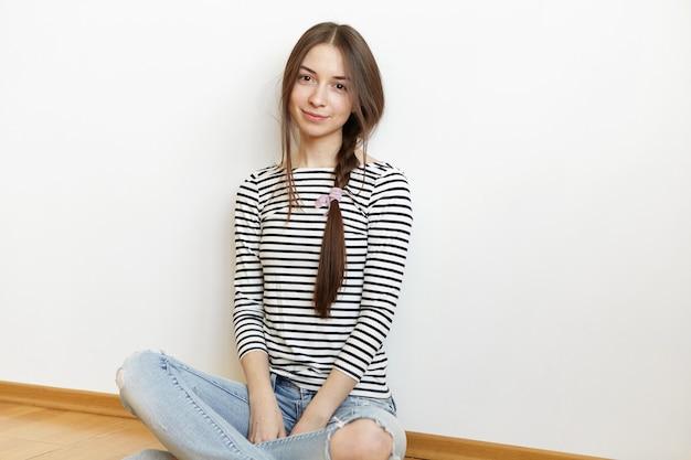 Foto interna de uma jovem encantadora com uma trança de cabelo bagunçado relaxando em casa depois da faculdade