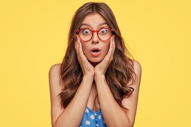 Foto interna de uma jovem espantada com óculos posando contra a parede amarela