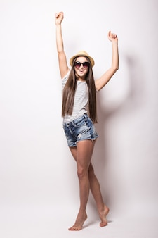 Foto interna de uma jovem europeia alegre fingindo dançar, usando uma blusa, chapéu e shorts da moda, recriada durante o verão