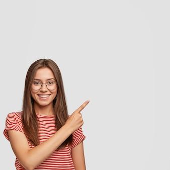 Foto interna de uma jovem europeia bonita com cabelo escuro e liso, sorriso encantador, apontando para o lado com o dedo indicador
