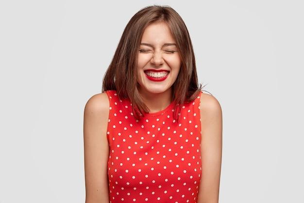 Foto interna de uma jovem européia satisfeita com uma aparência agradável e uma expressão alegre