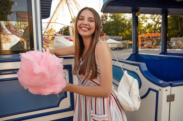Foto interna de uma jovem feliz e bonita mulher de cabelos compridos em um vestido leve de verão em pé sobre um parque de diversões em um dia quente com algodão doce na mão, olhando feliz e sorrindo amplamente