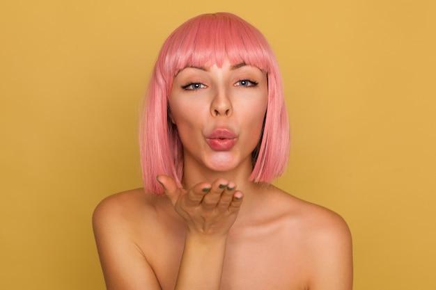 Foto interna de uma jovem linda de cabelos rosa de olhos azuis com corte de cabelo curto na moda, lábios dobrados no ar, beijo e soprando, posando sobre parede de mostarda com palma levantada
