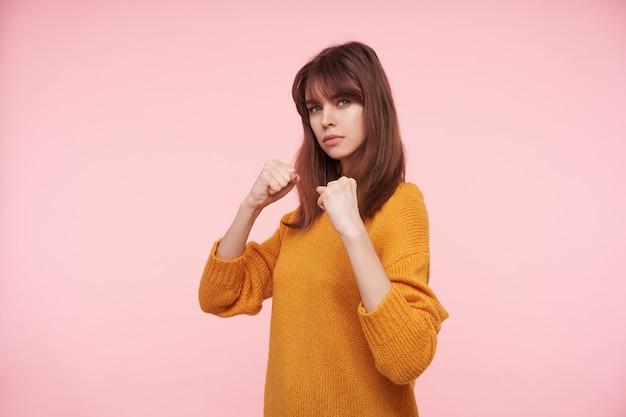 Foto interna de uma jovem linda morena com maquiagem natural e rosto calmo, em pé sobre a parede rosa em posição defensiva com os punhos erguidos