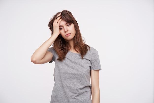 Foto interna de uma jovem linda morena segurando a mão levantada na cabeça e olhando cansada para baixo enquanto está de pé sobre um fundo branco em roupas casuais