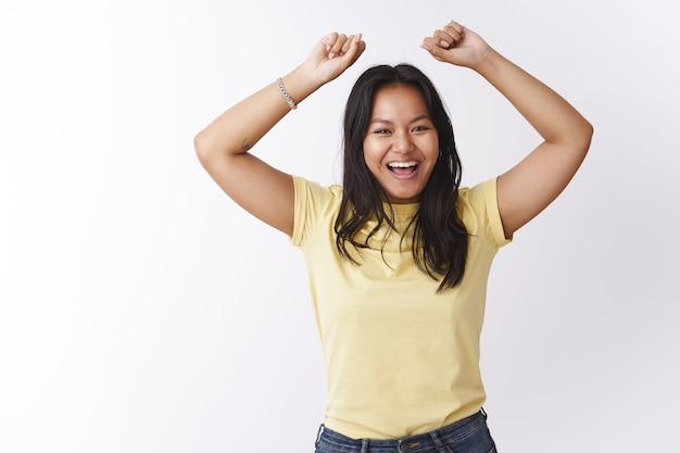 Foto interna de uma jovem malaia otimista, feliz e emotiva, pulando de brincadeira e rindo, sorrindo para a câmera e levantando as mãos, dançando alegremente e se divertindo de bom humor sobre uma parede branca
