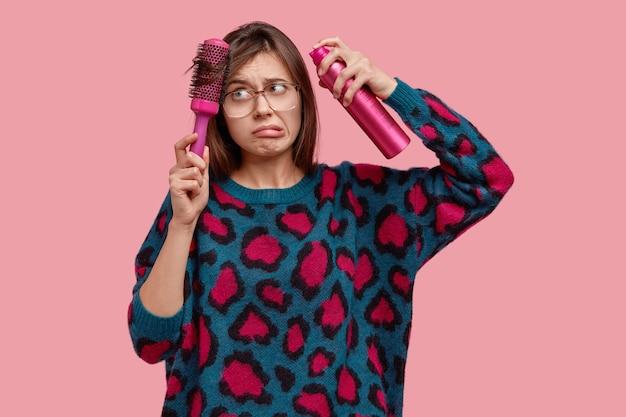 Foto interna de uma jovem modelo descontente com problemas com o cabelo, penteado, penteado com escova de cabelo, aparência frustrada