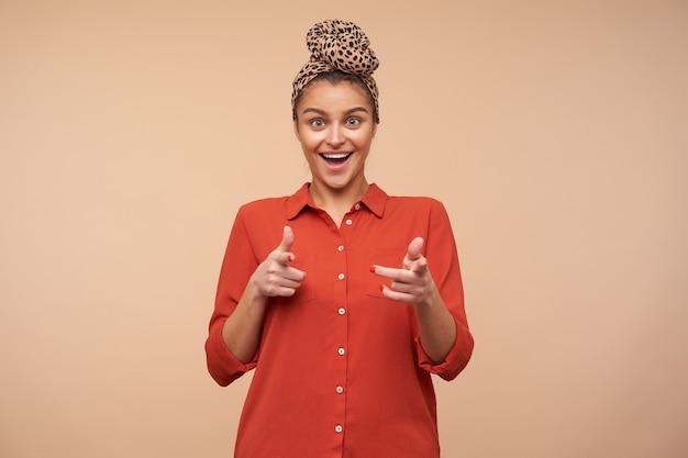 Foto interna de uma jovem morena alegre com fita na cabeça, mantendo as mãos levantadas, enquanto aponta alegremente para a frente com os indicadores, isolado sobre uma parede bege