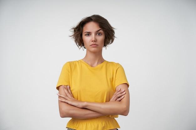 Foto interna de uma jovem morena com corte de cabelo curto, mantendo as mãos cruzadas sobre o peito, olhando e levantando uma sobrancelha confusamente, isolado