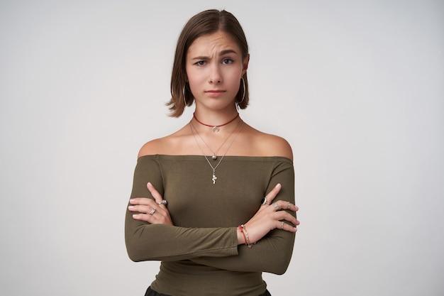 Foto interna de uma jovem morena confusa de cabelos curtos, levantando uma sobrancelha surpresa enquanto olha para frente e cruzando as mãos no peito, isolado sobre uma parede branca