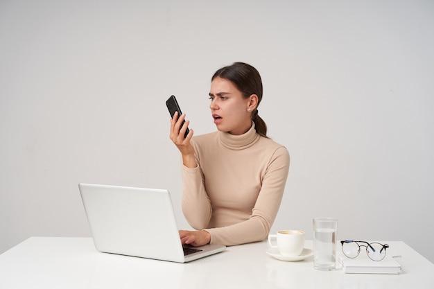 Foto interna de uma jovem morena descontente olhando para o aparelho com beicinho e fazendo careta, mantendo a mão no teclado enquanto está sentada na parede branca
