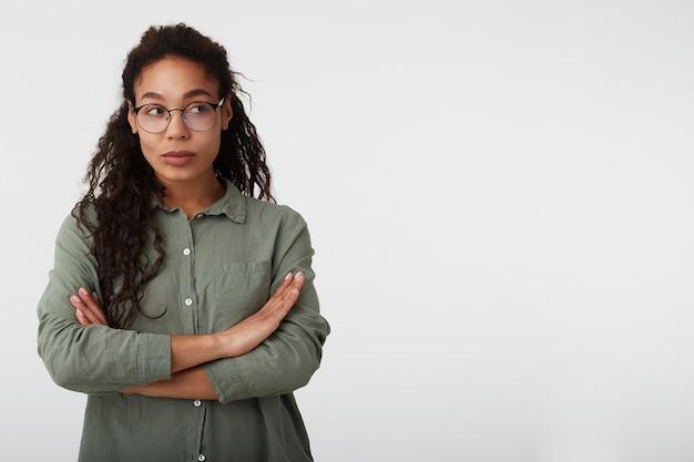 Foto interna de uma jovem morena encaracolada pensativa com pele escura, cruzando as mãos no peito enquanto olha para o lado com os lábios dobrados, posando sobre fundo branco