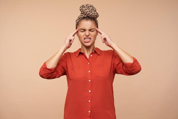 Foto interna de uma jovem morena vestida com camisa vermelha e bandana, franzindo a testa com os olhos fechados e mantendo ferofingers nas têmporas, posando sobre uma parede bege