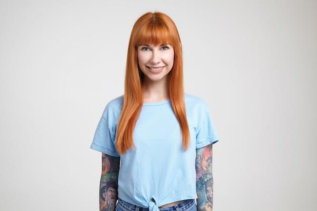 Foto interna de uma jovem mulher bonita de cabelos compridos com cabelo solto sexy, sorrindo alegremente enquanto olha alegremente para a câmera, isolada sobre um fundo branco em roupas casuais