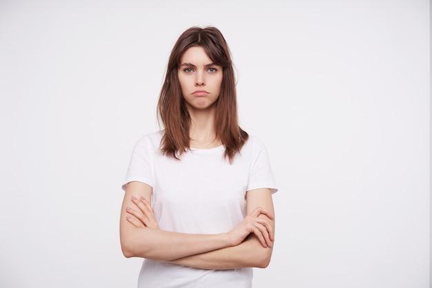 Foto interna de uma jovem mulher bonita morena cruzando as mãos no peito e olhando sério com os lábios dobrados, em pé contra uma parede branca