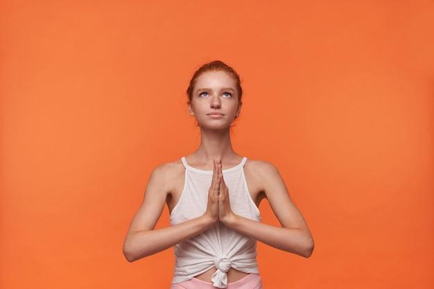 Foto interna de uma jovem mulher com penteado foxy, vestindo roupas casuais, olhando para cima com o rosto calmo, mantendo as mãos postas em gesto de namastê, posando sobre fundo laranja