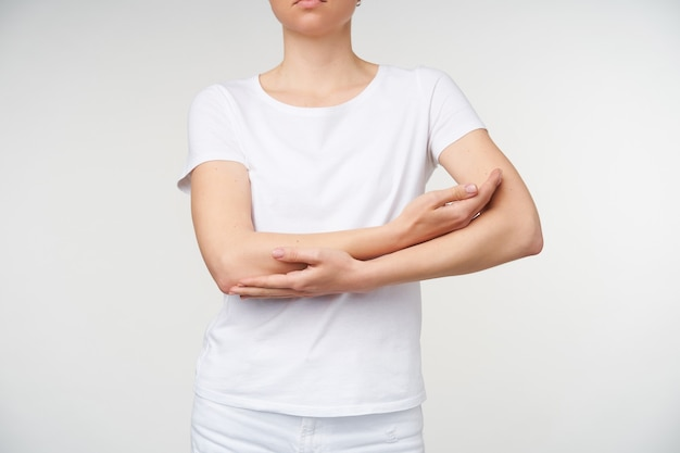 Foto interna de uma jovem mulher cruzando as mãos no peito enquanto imita uma criança embalada, em pé sobre um fundo branco em uma camiseta branca básica