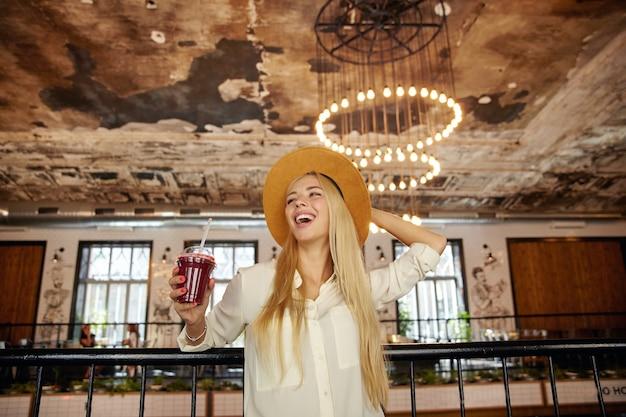 Foto interna de uma jovem mulher loira feliz com cabelo comprido, vestida com roupas da moda, posando no interior do café da cidade, segurando o chapéu e olhando para o lado com alegria, rindo de uma piada engraçada