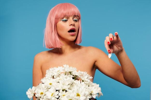Foto interna de uma jovem mulher nua de cabelo rosa com corte de cabelo bob posando em um enorme buquê de flores, olhando para a pétala da flor na mão levantada