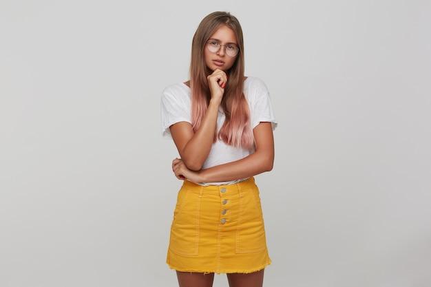 Foto interna de uma jovem mulher pensativa com cabelo castanho claro e comprido, parecendo séria enquanto apoia o queixo na mão levantada, em pé contra uma parede branca