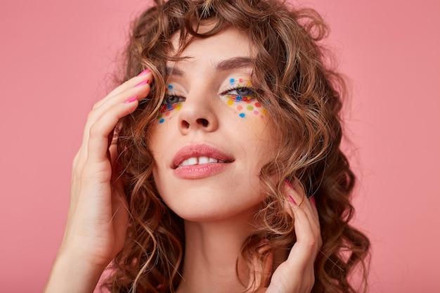 Foto interna de uma jovem romântica com cachos, tocando seu cabelo, com uma aparência sonhadora e satisfeita, sorrindo