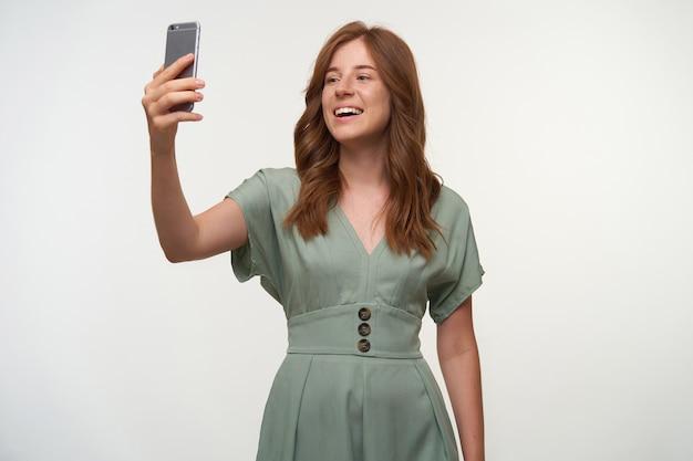 Foto interna de uma jovem ruiva alegre posando, fazendo uma foto de si mesma com o telefone, sorrindo feliz
