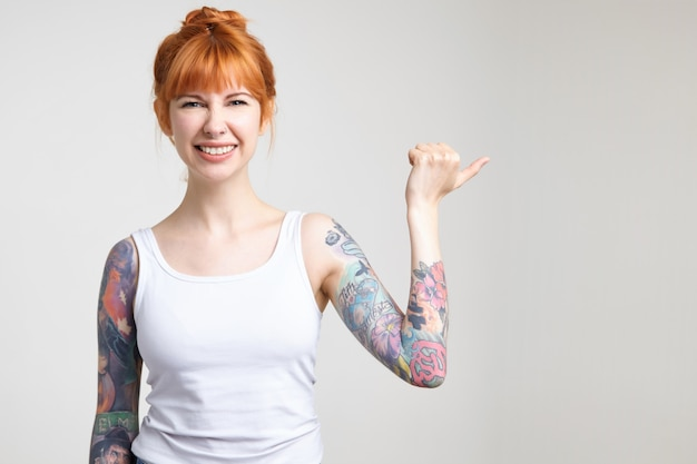 Foto interna de uma jovem ruiva atraente com tatuagens, franzindo a testa enquanto sorri e desliza o dedo para o lado com a mão levantada, isolada sobre fundo branco