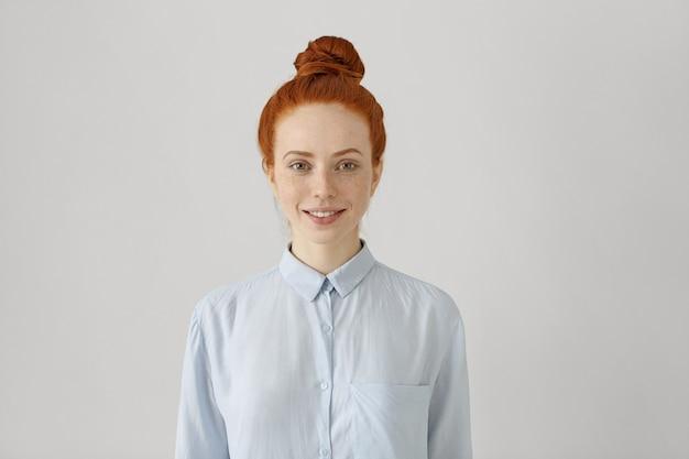 Foto interna de uma jovem ruiva atraente com um coque de cabelo na camisa e sorrindo alegremente