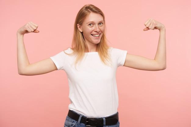 Foto interna de uma jovem ruiva bonita vestida com uma camiseta branca básica sorrindo amplamente para a câmera enquanto demonstra seus fortes bícepses, posando sobre um fundo rosa