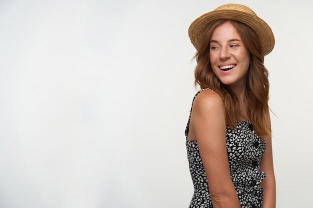 Foto interna de uma jovem ruiva charmosa com cachos olhando para o lado, feliz, em pé sobre um fundo branco com as mãos para baixo, usando um vestido romântico e chapéu de veleiro
