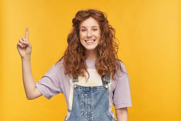 Foto interna de uma jovem ruiva vestindo um macacão jeans azul e uma camiseta roxa, apontando com um dedo para cima, sorrindo alegremente com uma expressão facial positiva