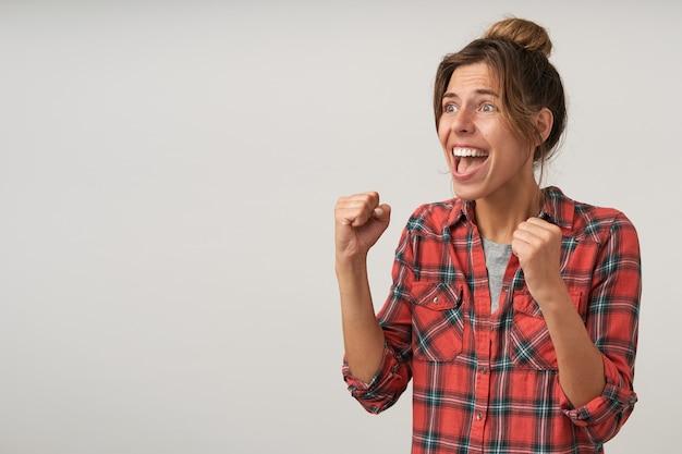 Foto interna de uma jovem senhora de cabelos castanhos vestida com roupa casual levantando as mãos enquanto olha animadamente para o lado e grita algo, isolada sobre fundo branco