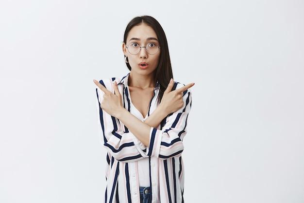 Foto interna de uma linda empresária espantada de óculos e blusa listrada, ficando fascinada e maravilhada em viagens turísticas, apontando para a direita e para a esquerda, franzindo os lábios de interesse e emoção