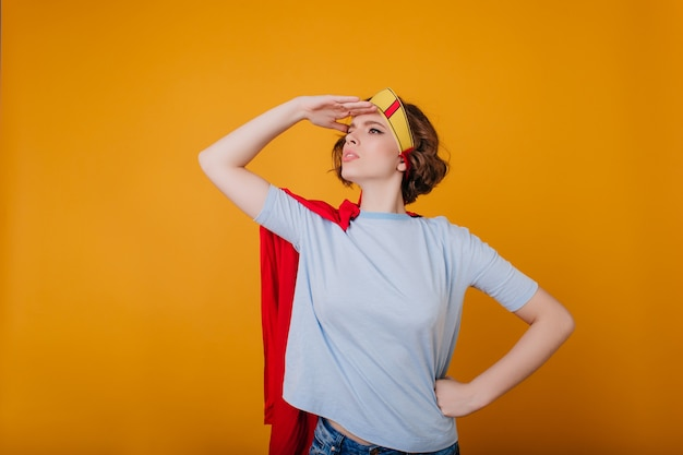 Foto interna de uma linda garota encaracolada com expressão de rosto corajoso posando na coroa