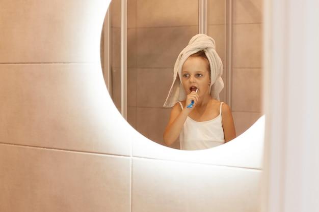Foto interna de uma linda garota garota escovando os dentes no banheiro, em frente ao espelho, enrolando a cabeça na toalha, procedimentos higiênicos pela manhã ou antes de ir para a cama