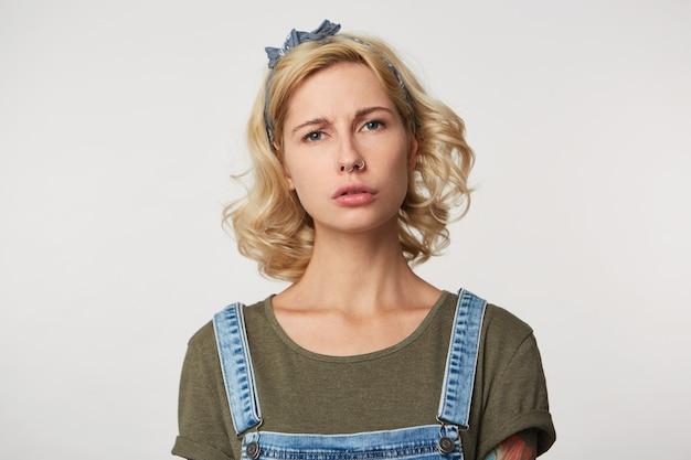 Foto interna de uma linda garota loira se sentindo triste e cansada, abusada por alguém, infeliz e furiosa com o cinza