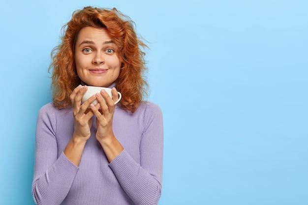 Foto interna de uma linda garota ruiva fazendo uma pausa para o café, segurando uma caneca branca com bebida aromática, sorri e olha, aprecia uma boa conversa enquanto bebe chá pela manhã, discute notícias