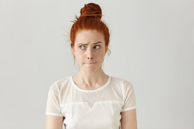 Foto interna de uma linda garota ruiva olhando para longe, com uma expressão facial duvidosa e indecisa