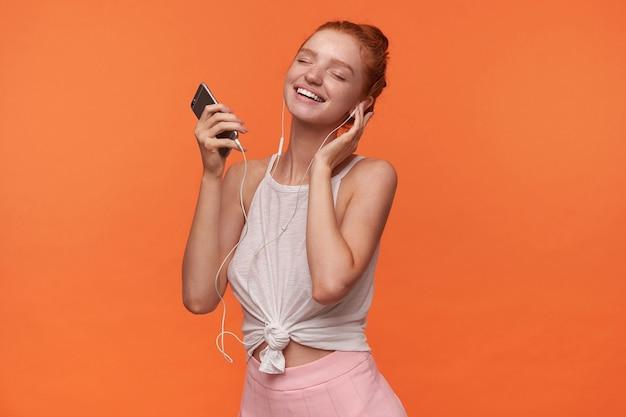 Foto interna de uma linda jovem com penteado foxy ouvindo música favorita, segurando a mão na orelha e sorrindo alegremente com os olhos fechados, posando sobre fundo laranja
