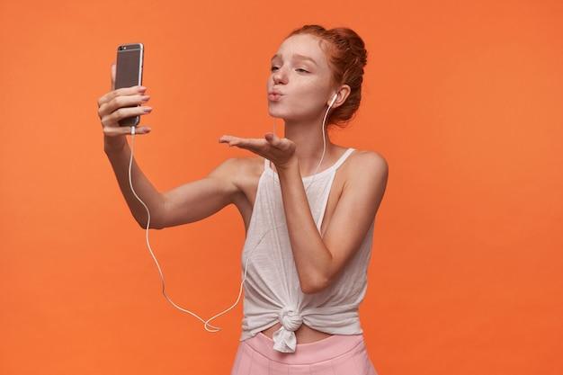 Foto interna de uma linda jovem com penteado sexy coque usando blusa branca e saia rosa, segurando o smartphone e fazendo uma foto de si mesma, enviando um beijo no ar para a câmera com uma cara positiva
